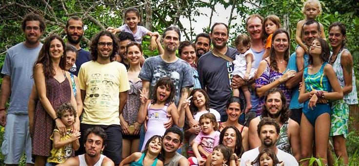 Grupo com cerca de 20 pessoas, de pé e agachadas, entre pais, professores e crianças, com a mata verde como fundo