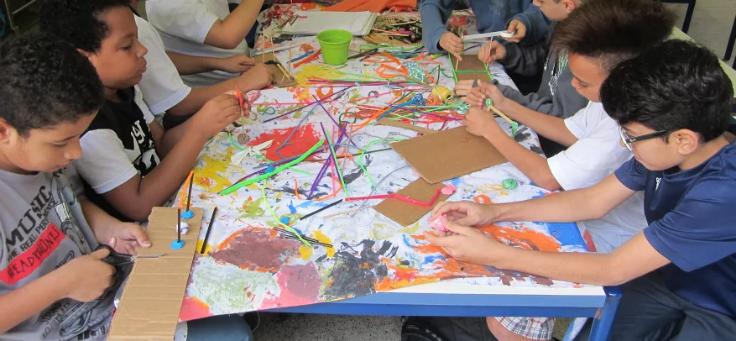 Crianças sentadas em mesa cumprida fazem pintura bem colorida sobre papel