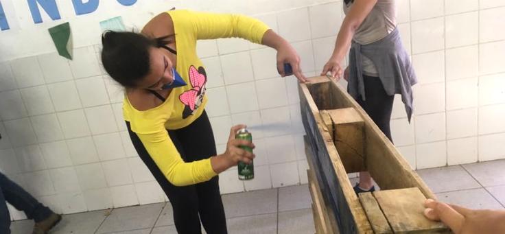 Adolescente constrói palco em escola. Ela está agachada pintando um pallet de madeira