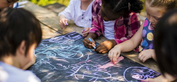 Cinco crianças brincam escrevendo com giz sobre lousa que está em cima de mesa