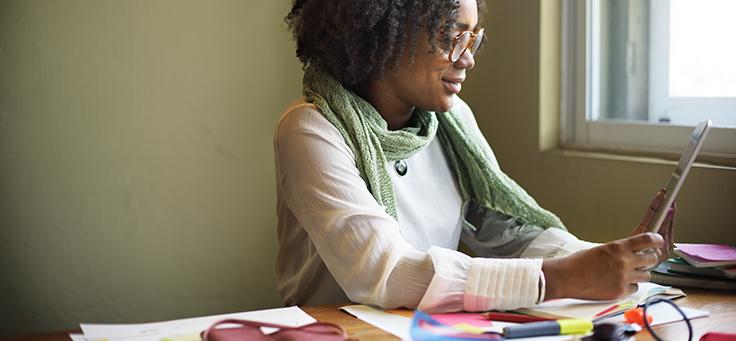 Mulher negra, na faixa dos 35 anos, sentada em cadeira, braços apoiados na mesa, manuseia tablet