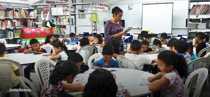 Professora circula em sala de aula com crianças sentadas em mesas circulares.