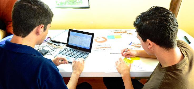 Dois jovens de costas sentados em uma cadeira apoiados em uma mesa, um com um net book, outro com uma caneta desenhando sobre uma cartolina