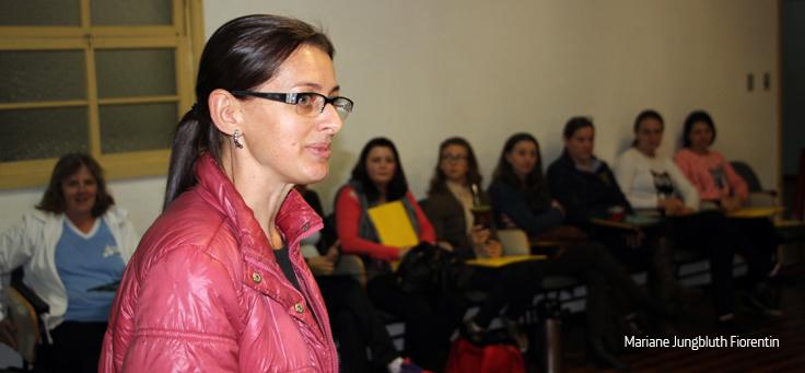 Moça de jaqueta vermelha e óculos está em pé em frente a algumas pessoas sentadas.