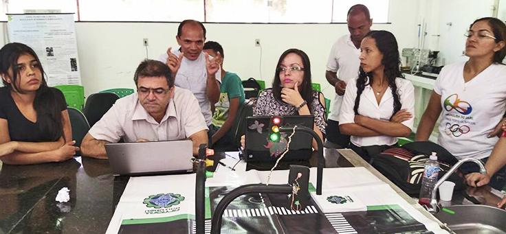 Participantes do projeto de robótica Tucuju durante aula diante de um computador