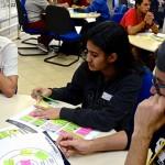 Três jovens empreendedores das ETECs sentados em uma mesa com papeis coloridos
