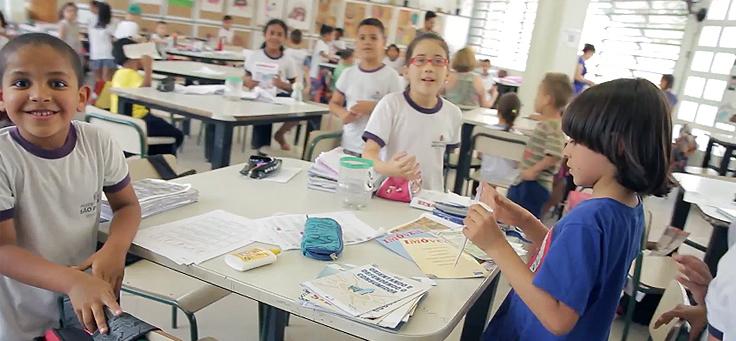 Grupo de crianças em torno de mesa compartilhada em sala de aula.