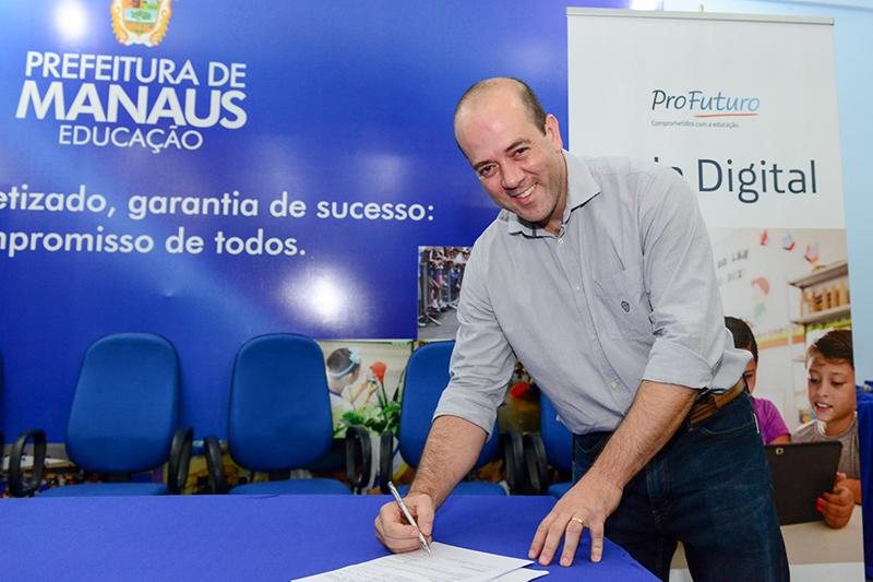 Presidente da Fundação Telefônica Vivo assina documento. Ele está de pé, e documento na mesa.