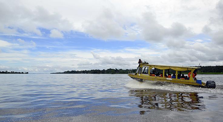 Barco amarelo navega por rio em Manaus