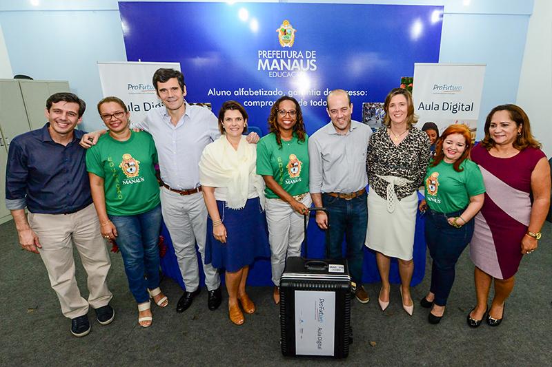Executivos da Fundação Telefônica, da Fundação Profuturo, secretária de Educação de Manaus e outras pessoas tiram foto lado a lado. À frente, está a maleta do projeto Aula Digital.