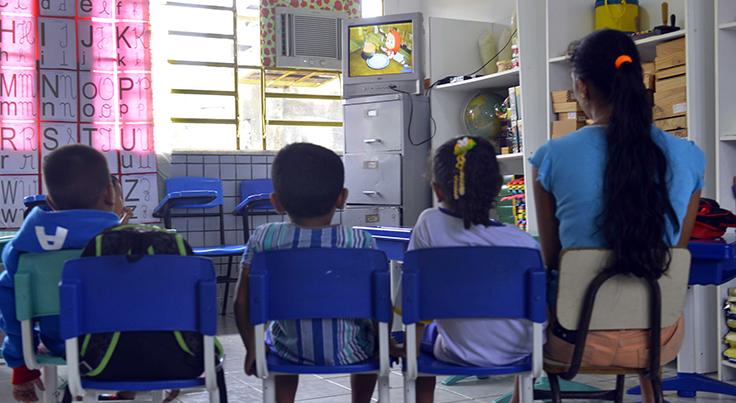Três crianças sentadas ao lado da professora assistem a vídeo em televisão