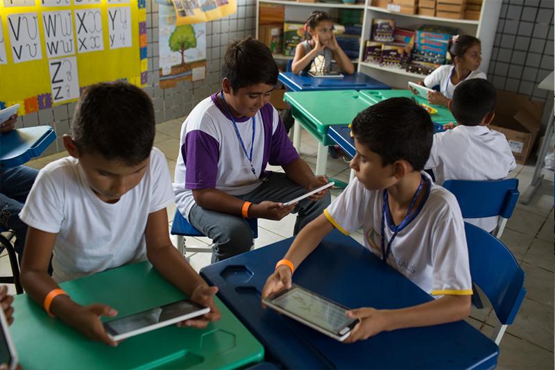 Três crianças brincam com tablets sentadas em suas carteiras na sala da escola Nossa Senhora do Carmo.
