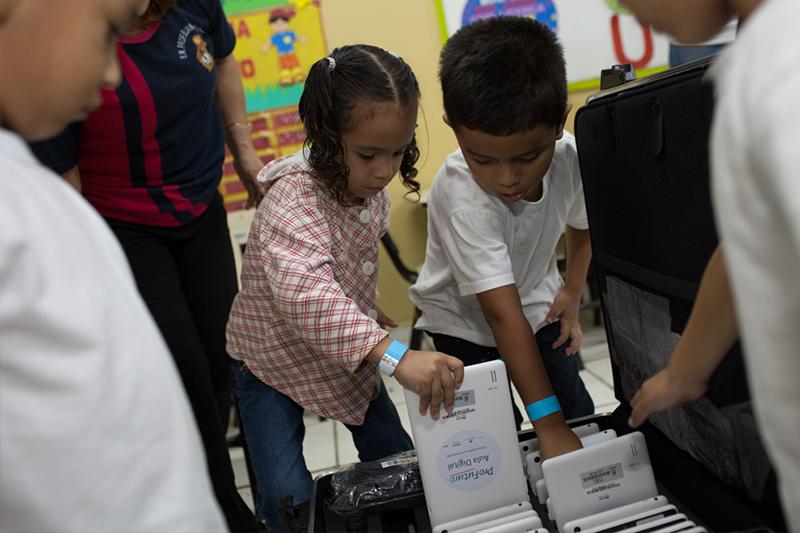Dois alunos da EMEF Eliana Pacheco abrem maletas do Projeto Aula Digital