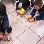 Texto Alternativo Três garotos brincam no chão com robôs criados a partir de matérias que iam patrão lixo