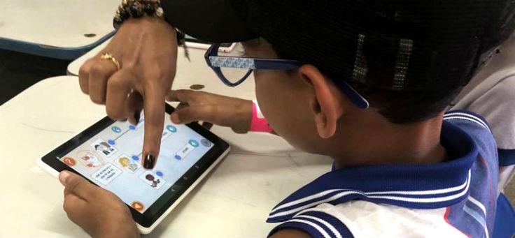 Alunos da Escola Estadual General Calazans, na cidade de Nossa Senhora das Dores (SE), sentados prestam atenção em tablet do Aula Digital