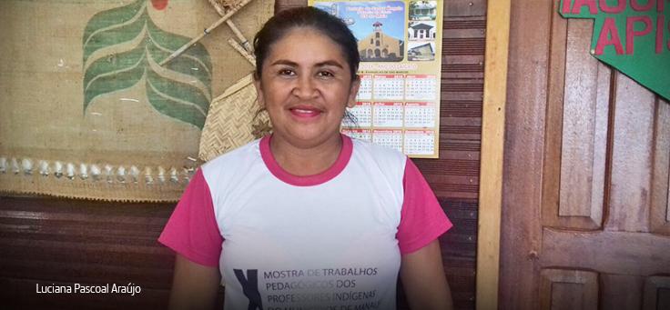 Em imagem horizontal, professora indígena Luciana Pascoal Araújo, de camiseta branca e rosa no ambiente escolar