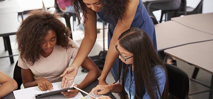 Jovem negra e jovem oriental sentadas em cadeira e apoiadas em mesa recebem orientação de uma pessoa que está de pé e inclinada sobre elas