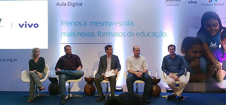Representantes da Fundação Telefônica Vivo e da Secretaria Estadual de Educação de Sergipe em palco com iluminação reduzida e azulada para apresentação do projeto aula digital