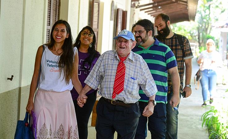Senhor caminha de mãos dadas com voluntária por lar de idosos