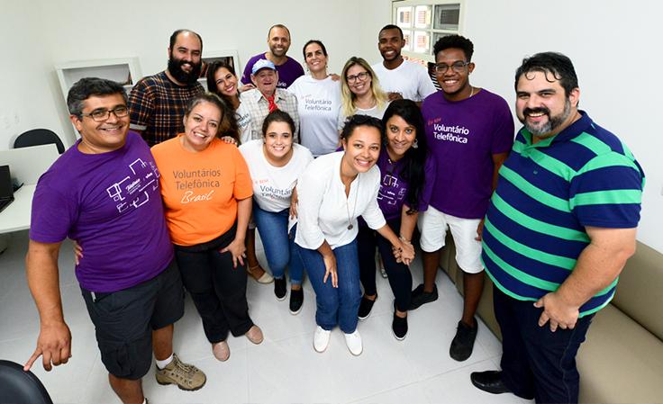 Voluntários e funcionários de pé posam para foto