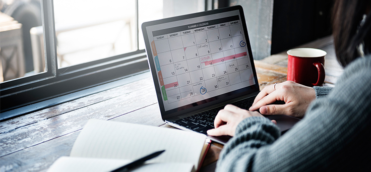 Mulher olha para computador em que aparece a imagem de um calendário.