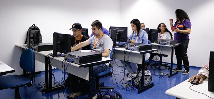 Imagem mostra pessoas sentadas olhando para a tela de um computador