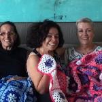 Margarete, a segunda da direita para a esquerda, e suas amigas seguram manta feita com os quadrinhos de lã