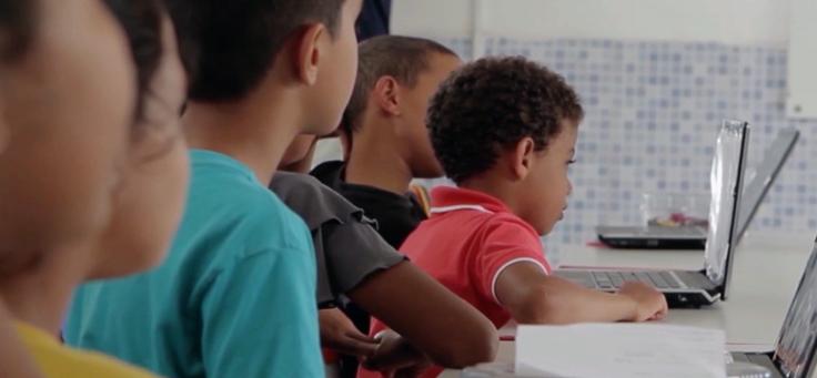 A imagem mostra três crianças olhando para a tela de um computador