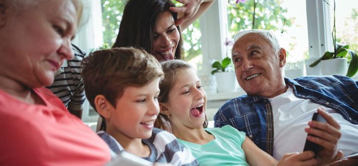 Duas crianças sorriem ao segurar um smartphone, assim como um idoso e uma mulher adulta