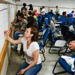 Participantes de encontro estão em pé e escrevem em cartazes afixados nas paredes em uma sala