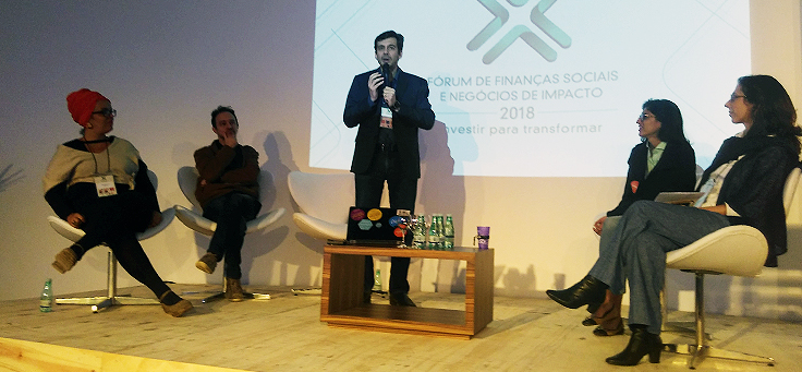 Homem em pé debate em palestra, rodeado por três especialistas