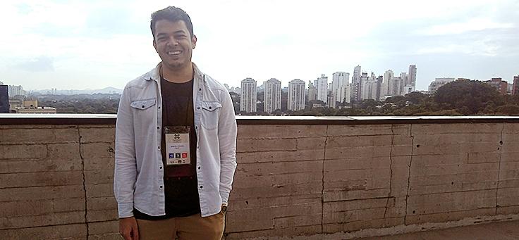 Homem sorridente posa para foto com paisagem de prédios de São Paulo ao fundo