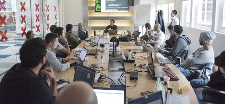Imagem mostra pessoas em volta de uma mesa em projeto ensina programação para refugiados na Holanda