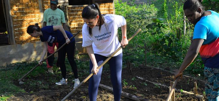 pessoas voluntárias do Grupo Telefônica participam do Vacaciones trabalhando em área de terra