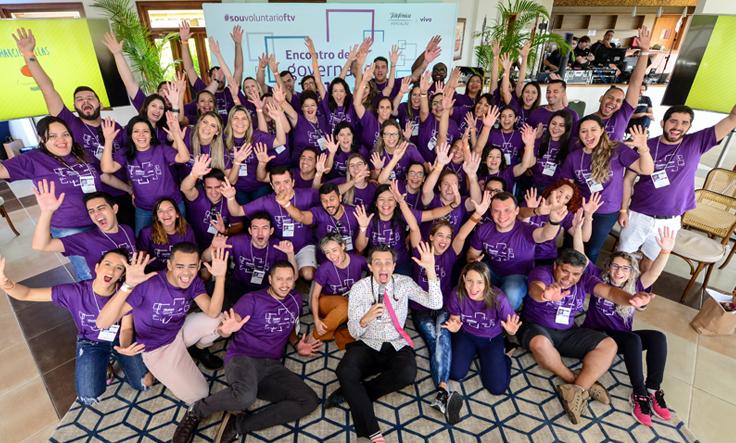 Voluntários do Grupo Telefônica Vivo formam círculo e posam para foto usando camisas na cor roxa