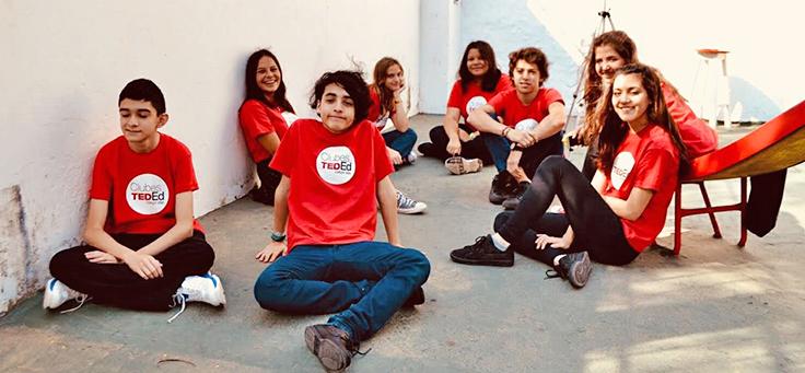 Alunos sentados em pátio escolar usando a camiseta onde se lê TED