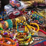 Foto mostra diversos itens como colares e lenços coloridos em uma bancada da Feira Preta, evento que recebe e incentiva empreendedores negros em São Paulo