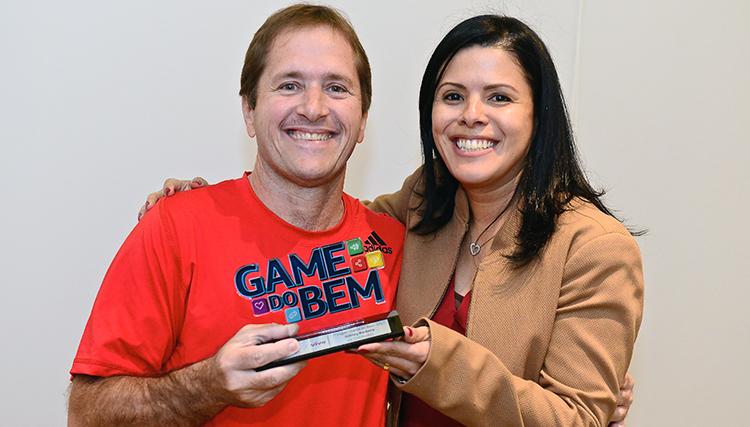 Imagens mostram tela do Game do Bem e de dois vencedores do jogo com Luanda de Lima Sabença, gerente de Comunicação e Voluntariado