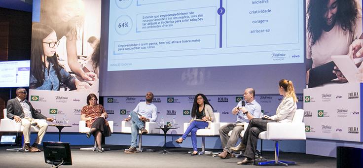 Imagem mostra uma das mesas do evento Inovação Educativa, promovido pela Folha de São Paulo. Há seis palestrantes sentados em semicírculo em cima do palco