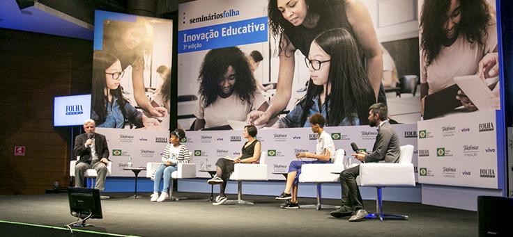 Palestrantes aparecem sentados em semicírculo, em cima do palco, durante debate sobre diversidade no 3º Seminário de Inovação Educativa da Folha