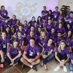 Mais de 20 colaboradores do Programa de Voluntariado da Fundação Telefônica Vivo aparecem agrupados, usando camiseta púrpura e sorrindo para foto