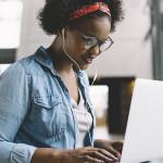 Na imagem, mulher aparece usando notebook e usando fones de ouvido. Ela é negra, tem cabelos cacheados e preços com lenço e está sorrindo.