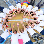Na imagem voluntários do Vacaciones Solidárias estão deitados no chão formando um círculo, com braços e pernas esticados