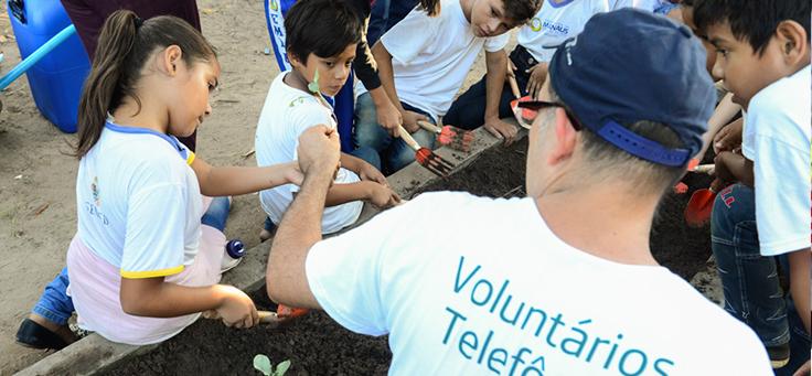 Voluntário aparece ao lado de crianças em ação de manutenção da horta da Escola Municipal Lili Benchimol