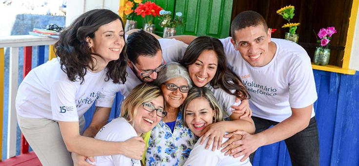 Voluntários do Vacaciones Solidárias rodeiam e abraçam educadora em ação na sala de leitura da Escola Municipal Lili Benchimol