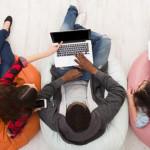 Imagem mostra jovens sentados em pufes mexendo em notebooks