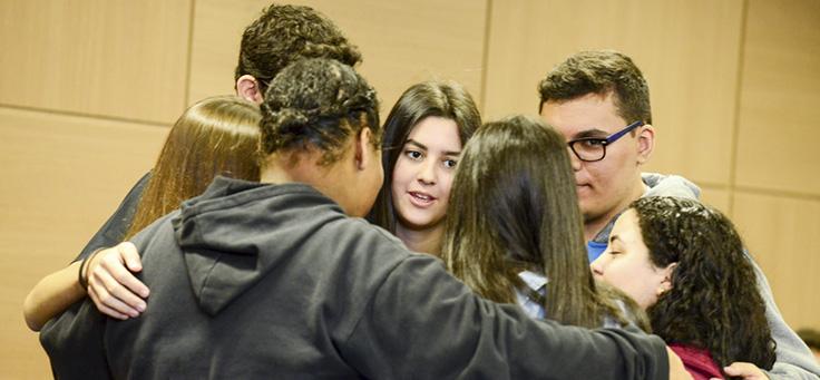Na imagem, grupo de jovens do programa Pense Grande se abraça coletivamente, formando um círculo