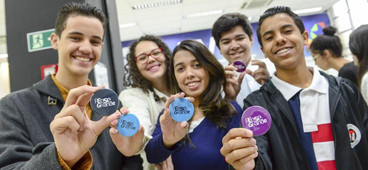 Na imagem, grupo de jovens do Programa Pense Grande mostra broches do programa Pense Grande