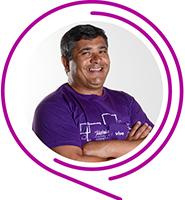 Zacarias, do Programa de Voluntariado da Fundação Telefônica Vivo, usa camiseta púrpura, tem cabelos grisalhos e sorri