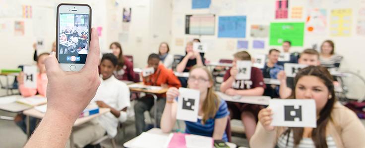 Professor segura celular em frente a classe de alunos